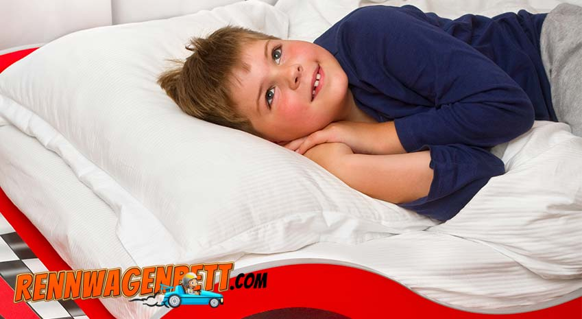 kleiner Junge in rotem Rennwagenbett