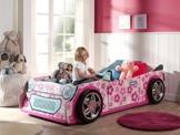 kleines Rennwagenbett für Mädchen in rosa im Kinderspielzimmer mit Mädchen sitzend auf dem Bett
