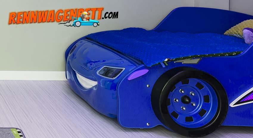 Ein blaues Rennwagenbett mit blauer Decke im Kinderzimmer