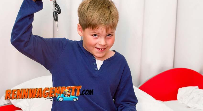 kleiner Junge mit blauem Schlafanzug sitzt auf seinem roten Autobett und hält schelmisch grinsend die Autoschlüssel in der Hand