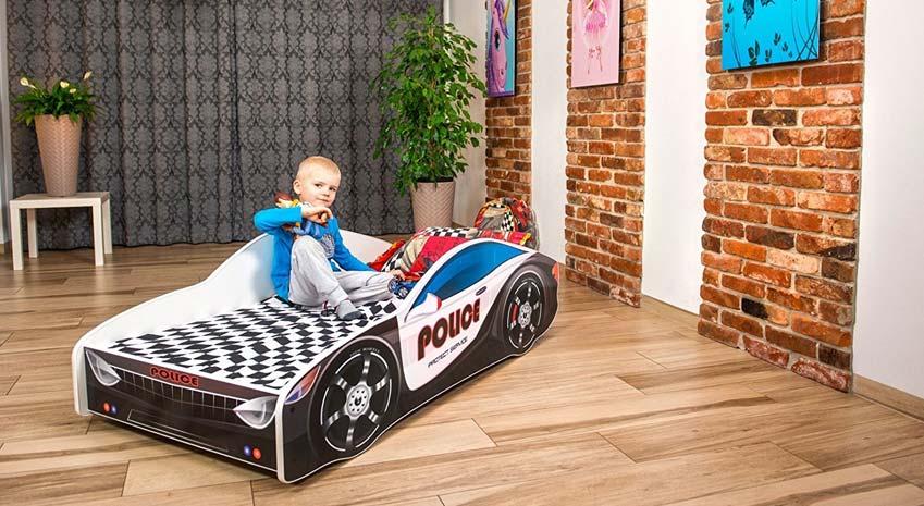 Polizeiautobett für Kleinkinder in Zimmer mit kleinem jungen darauf